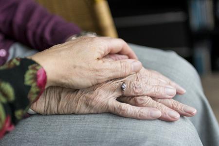 Tochter hält die Hände ihrer alten Mutter