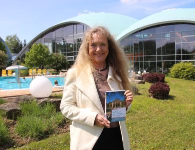 """Marion Schneider, geschäftsführende Gesellschafterin der Toskanaworld, mit dem Buch """"Kurbäder im Herzen Europas"""" / Foto: Klaus Lohmann"""