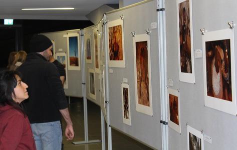"""Besucherinnen und Besucher bestaunen die Bilder der Fotoausstellung """"Undress your Soul"""" über die indigenen Völker Namibias  (Foto: Lisa Streeb)"""