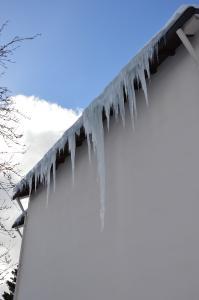 """Schöner, aber gefährlicher """"Eiszauber"""", der durch einen fehlenden Schneefang entstehen konnte.  Auch solche Eislasten sollten nur vom Dachdecker sicher entfernt werden"""