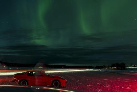 Farbenprächtiges Polarleuchten am Nordkapp. Die Auffahrt zu einer Brücke ähnelt einer Sprungschanze