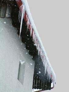 Eisbildung kann ein Hinweis auf verstopfte Fallrohre und nicht gereinigte Dachrinnen sein.