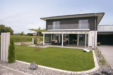 Das Muster Haus der Firma Fink Haus in Altshausen ist ein KfW-40-Plus-Effizienzhaus. Passend zur energetisch umweltfreundlichen und zukunftssicheren Philosophie mit eigener Stromerzeugung und der Nur-Strom-Haustechnik sorgt ein strombetriebener Rasenmäherroboter für das gepflegte Grün