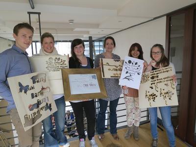 """Studierende des Studiengangs Industrial Design zeigen die Holzschablonen und Drucke, die im Workshop """"Experimentelle Typographie"""" entstanden sind"""