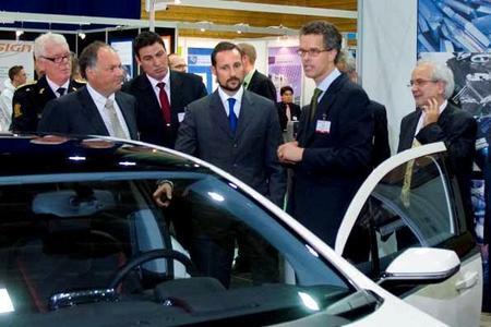 Kronprinz Haakon von Norwegen (Mitte) im Gespräch mit Chefingenieur Frank Weber, der die Funktion des elektrischen Opel Ampera erläutert