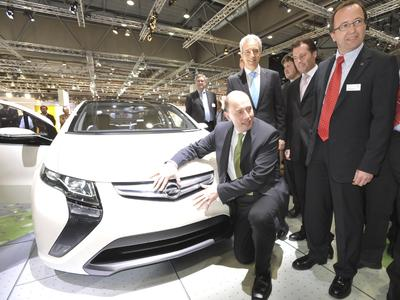 Zu Gast auf dem Opel-Stand bei der AMI Leipzig: Verkehrsminister Wolfgang Tiefensee lädt den elektrischen Opel Ampera, flankiert von Stanislaw Tillich, Ministerpräsident des Freistaats Sachsen (links) und Opel-Vertriebsdirektor Michael Klaus
