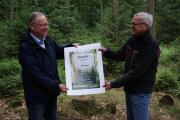 Schirmherr der Klima-Aktion Wald, Ministerpräsident Stephan Weil, nimmt die erste Klima-Aktie von Dr. Klaus Merker, Präsident der Niedersächsischen Landesforsten, entgegen