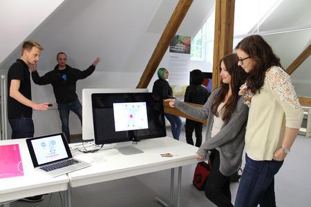 Die Zweitsemester Linnea Helms (2.v.r.) und Tobias Düser  (links) zeigen Messegästen ihr interaktives Spiel für Jung und Alt