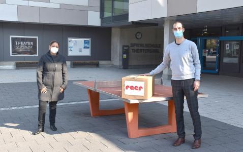 Tobias Mörk, reer GmbH, überreichte am Mittwochmorgen ein großes Paket mit 600 Mundschutzmasken an Frau Khalegi, Vorstand des Fördervereins der Spitalschule.