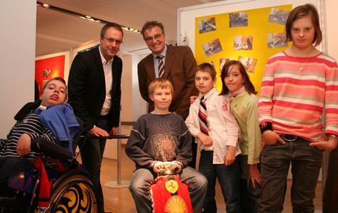 """Schulleiter Jochen de Vries (hinten links) und Regionspräsident Hauke Jagau (hinten rechts) eröffneten im Haus der Region die Ausstellung """"Crazy Chairs"""" der Janusz-Korczak-Schule aus Springe"""
