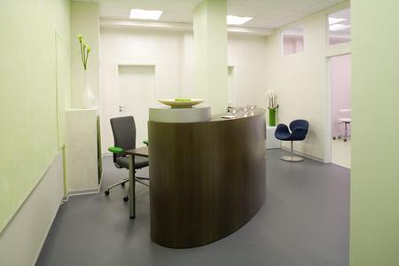 Der Empfangsbereich der Praxis präsentiert sich in zarter, frischer Farbigkeit. Der dunkle, organisch geformte Tresen steht entschieden und selbstbewußt frei im Raum.