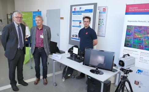 IHP-Geschäftsführer Bernd Tillack (l.) am Stand der TH Wildau mit Prof. Dr. Sigurd Schrader (MItte) und Christian Breiler / Fotograf / Quelle: FG Photonik