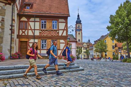 """Wanderer auf dem LTM5 """"Kirchen und Kleindenkmale"""" am Schlossplatz in Tauberbischofsheim. Im Hintergrund der Turm der Stadtkirche St. Martin. Foto: Tourismusverband Liebliches Taubertal / Peter Frischmuth"""