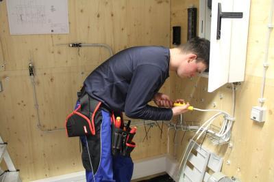 Thomas Schönliner, Sieger des Nationalwettbewerbs Anlagenelektrik, von der Milchwerke Berchtesgadener Land Chiemgau eG aus Piding ist konzentriert auf das Verlegen von Stromkabeln zum Schaltschrank.