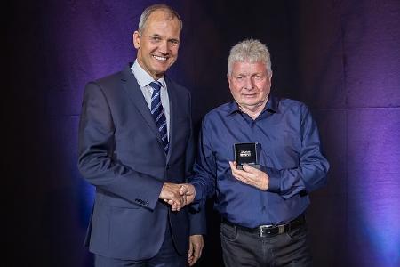 Michael Wendt (l.), Vorsitzender der Geschäftsführung Pirelli Deutschland, gratuliert Ottmar Beck zum 50-järigen Dienstjubiläum