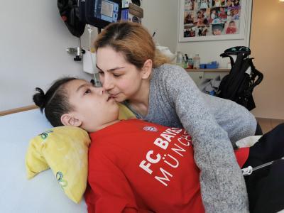 Ein Junge liegt mit offenen Augen im Bett. Seine Mutter beugt sich über sein Gesicht.