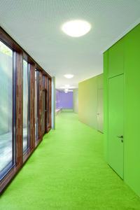 Eine Abfolge von Grüntönen adressiert die Eingangsbereiche der Klassenzimmer. Der Eingangsgrünton findet sich an der flurseitigen Wand im Raum wieder