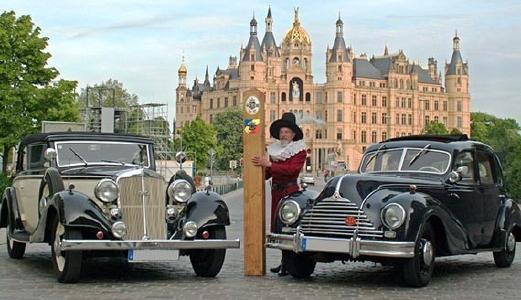 Zwei Oldtimer (Horch und EMW) vor dem Schweriner Schloss mit Mann in historischer Uniform