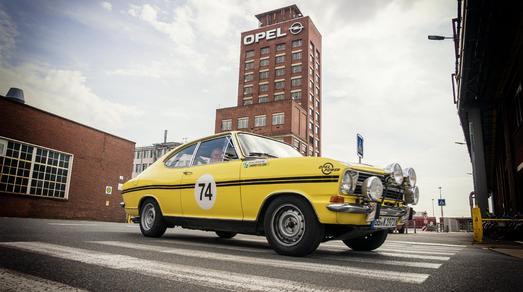 """Werksfahrer: Der Opel Kadett B """"Kulläng"""" mit Rennfahrer-Legende Jockel Winkelhock und Opel-Kommunikationsdirektor Harald Hamprecht kurz vor dem Mittagsstopp im Opel-Werk Rüsselsheim"""