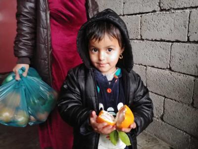 Dieses jesidische Flüchtlingskind im Nord-Irak freut sich über das frische Obst aus der ersten Verteilaktion von Shelter Now