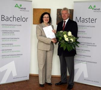 AKAD-Geschäftsführer Harald Melcher (re.) überreicht Eva Schwinghammer (li.) die Urkunde zur Professur.