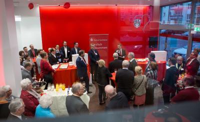 Landrat Ulrich Krebs (Bildmitte), Frederik Zölls, Marktbereichsleiter der Taunus Sparkasse im Hochtaunuskreis (rechts mit Mikrophon), und Thomas Blasini (links) begrüßten die knapp 130 Gäste, die zur Filialeröffnung gekommen waren