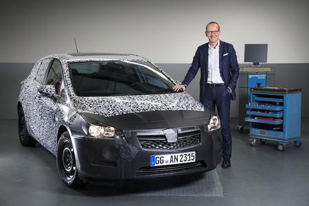 Stolzer Moment: Opel-Chef Dr. Karl-Thomas Neumann präsentiert einen noch stark getarnten Astra-Prototypen der neuen Generation. Foto Opel AG