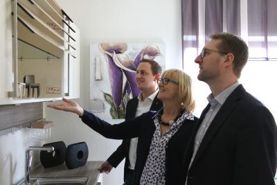 Bürgermeister Bach und Wirtschaftsdezernent Mischak sind fasziniert von der Schließtechnik eines Küchenschranks, die Christa Künstler vorführt, Foto: Gaby Richter, Vogelsbergkreis
