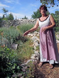 Pensionswirtin Sonja pflanzt im Kräutergarten Salbei und andere Kräuter an.
