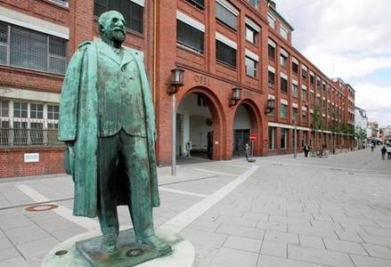 Industrie-Denkmal: Adam-Opel-Statue vor dem Hauptportal des historischen Opelwerks im Zentrum von Rüsselsheim