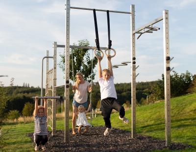 Die ganze Familie trainiert an einer Fitness-Station im eigenen Garten.