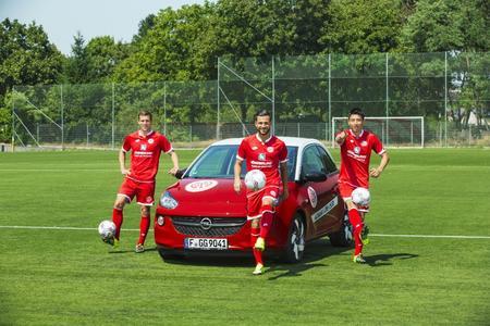 Gute-Laune-Fußballer: Die Mainzer Fabian Frei, Danny Latza und Ja-Cheol Koo mit dem Opel ADAM in den Vereinsfarben der Rheinhessen. Foto Adam Opel AG