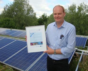 Dr. Martin Nägele demonstriert im Rahmen der Aufnahme stolz die eigene Photovoltaik-Anlage.