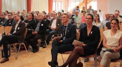 """Dr. Elisa Stickler und Maria Münzel informierten beim Vogelsberger Gesundheitsforum über das Projekt """"Gemeindeschwester 2.0"""". Moderiert wurde der Abend von Ulf Werner (OptiMedis AG), begrüßt wurden die Gäste von Erstem Kreisbeigeordneten Dr. Jens Mischak (erste Reihe, von rechts). Foto: Sabine Galle-Schäfer/Vogelsbergkreis"""