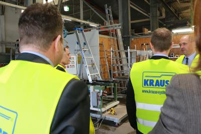 """Abteilungsleiter Jürgen Steinbrecher (hinten rechts) erklärt den Produkttest der Stehleiter im Hintergrund: Etwa eine Woche lang steht sie auf unebenem Grund und wird mit 150 kg Gewicht wechselseitig 50.000 mal """"betreten""""!, Foto: Gaby Richter"""