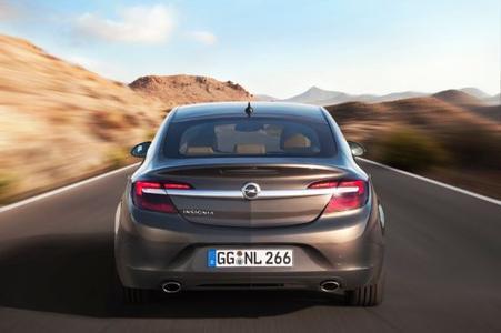 Die Heckpartie des neuen Opel Insignia wirkt breiter und tiefer als zuvor. Die Chromspange mit Opel-Markenemblem zieht sich bis weit in die zweitgeteilten Rückleuchten