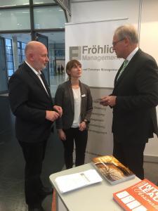 Foto 1: Im Gespräch: Edmund Fröhlich (li.) und Manuela Dabitsch von Fröhlich Management informierten Richard Bartsch, Bezirkstagspräsident von Mittelfranken, an ihrem Stand. Foto: FM