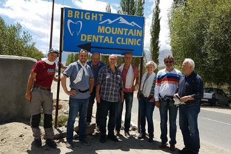 """Otmar Knoll, Direktor von Whirlpools World und Whirlcare Industries aus Deißlingen-Lauffen (Zweiter von rechts), mit Dr. Rainer Roos (Vierter von links), Geschäftsführer und Gründer der gemeinnützigen Ladakh Medical Aid gGmbh, vor dem Eingang zur """"Bright Mountain Dental Clinic"""" in Choglamsar."""