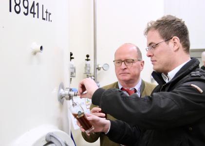 Braumeister Josef Erl (vorn) und sein Onkel Günter Erl prüfen den Reifegrad eines dunklen Biers, das in einem der rund 19.000 Liter fassenden Tanks lagert. Foto: obx-news/Jens Henning-Billon