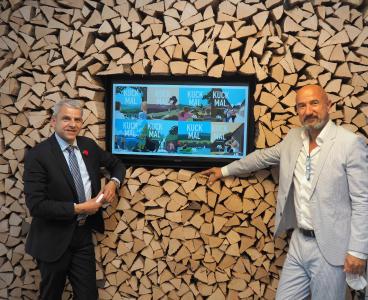 Tourismusstaatssekretär Herrn Dr. Rapp (links) und STG-Geschäftsführer Hansjörg Mair mit Motiven der aktuellen Kuck Kuck-Kampagne