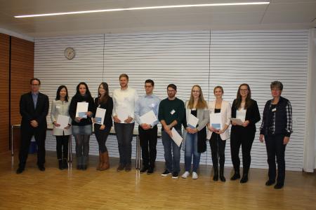 Das Bild zeigt eine Gruppe der diesjährigen Stipendiatinnen und Stipendiaten mit ihren Urkunden, flankiert von Jürgen Todt und Andrea Henninger, die das Deutschlandstipendium an der Hochschule Ludwigshafen betreuen