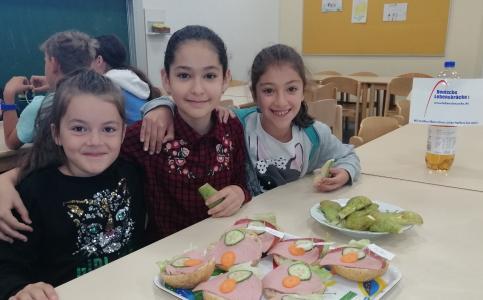 3 Mädchen sitzen am Frühstückstisch vor belegten Semmeln und lächeln.