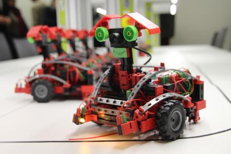 Fahrbare Roboter aus einer Modellbaureihe von Fischertechnik können mit unterschiedlichen Sensoren bestückt sowie mittels PC, Tablet oder Smartphone-App programmiert und gesteuert werden. So lassen sich verschiedenste Straßenverkehrssituationen simulieren und Anforderungen an zukünftige Systeme zum autonomen Fahren vermitteln / Fotograf / Quelle: TH Wildau / Bernd Schlütter