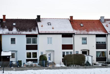 Sichtbarer Unterschied der Dämmung bei annähernd baugleichen Gebäuden: Während beim mittleren, gut gedämmten Haus der Schnee auf dem Dach liegen bleibt, ist die Schneedecke bei den bei-den anderen Dächern abgetaut
