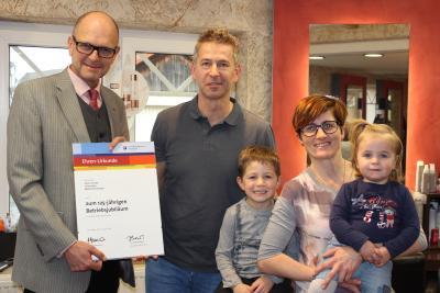 Hauptgeschäftsführer Dr. Joachim Eisert bei der Überreichung der Ehrenurkunde an Oliver Stumpp sowie Ehefrau Karin mit Kindern