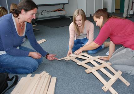 Von Leonardo entwickelt, von den Realschülerinnen Elisabeth (Mitte) und Antje (rechts) ausprobiert. Mit Unterstützung von Judith Bräuer von der HS Osnabrück versuchten die beiden Teilnehmerinnen des MINT-Kurses, eine möglichst große und stabile Brücke zu bauen - ganz ohne Nägel