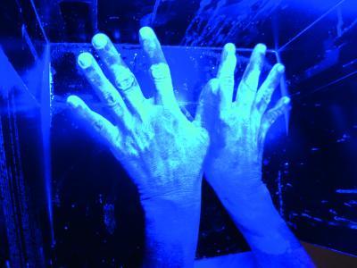 Unter Schwarzlicht zeigt es sich, ob die Hände richtig desinfiziert wurden