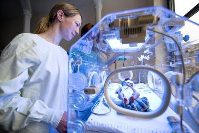 Eine Kinderkrankenschwester erläutert einer Mutter die aktuelle Situation ihres Frühgeborenen unter der Phototherapie