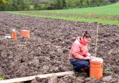 Maike Krauss is measuring greenhouse gasses on a ploughed plot; visible in the background is a plot cultivated with reduced tillage (Photo: FiBL, Thomas Alföldi)