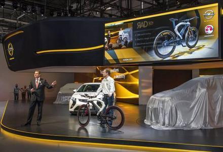 Weltpremiere eines Sportlers:Die Führungsrolle von Opel im Bereich Elektromobilität unterstrich Vorstandsvorsitzender Karl-Friedrich Stracke zur Eröffnung des Genfer Automobilsalons. Links der Ampera, das ' Auto des Jahres 2012', rechts das Opel RAD e, ein nach automobilen Konstruktionsprinzipien gebautes Elektro-Rad, das in Genf Premiere feiert